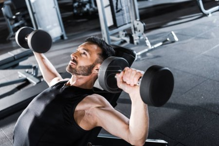 Photo for Selective focus of handsome strong man working out with dumbbells in gym - Royalty Free Image