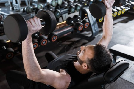 Photo for Overhead view of handsome strong man working out with dumbbells in gym - Royalty Free Image