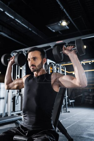 Photo for Low angle view of strong man working out with dumbbells in gym - Royalty Free Image