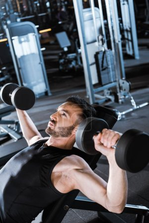 Photo for Selective focus of strong bearded man working out with dumbbells in gym - Royalty Free Image