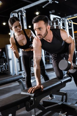 Photo for Low angle view of attractive trainer standing near handsome man working out with dumbbell - Royalty Free Image