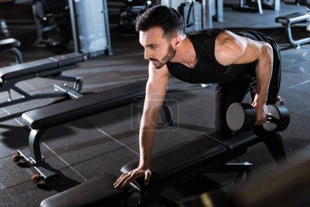 Photo pour Mise au point sélective de sportif barbu de travailler avec haltère dans la salle de gym - image libre de droit