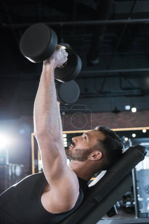 Photo for Low angle view of happy man working out with dumbbells in gym - Royalty Free Image