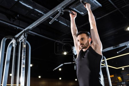 Photo for Low angle view of strong athletic man doing pull up in sports center - Royalty Free Image