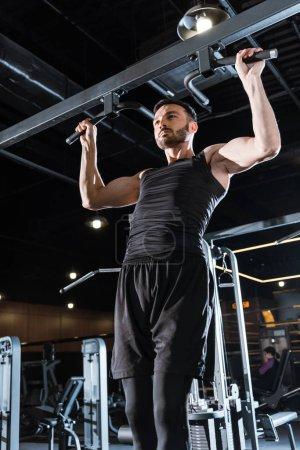Photo pour Vue à angle bas du sportif athlétique faisant tirer vers le haut dans le centre sportif - image libre de droit