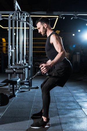Photo pour Beau homme athlétique s'exerçant sur l'appareil d'entraînement dans la gymnastique - image libre de droit