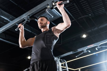Photo for Low angle view of handsome sportsman doing pull up in sports center - Royalty Free Image