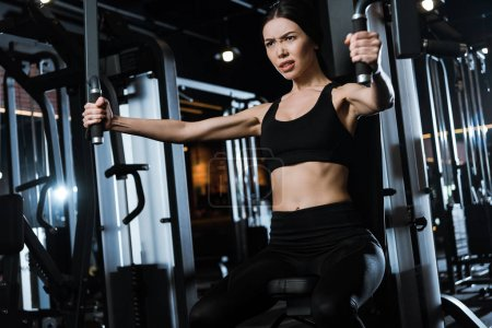 Photo for Athletic sportswoman exercising on training apparatus in gym - Royalty Free Image
