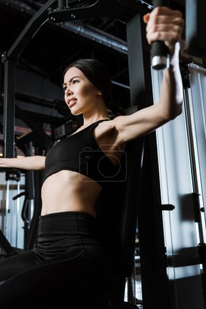 Photo for Low angle view of sportswoman in sportswear exercising on training apparatus in gym - Royalty Free Image