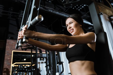 Photo for Low angle view of strong sportswoman in sportswear exercising on training apparatus in gym - Royalty Free Image