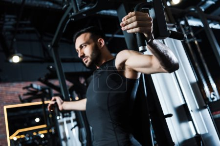 Photo for Low angle view of strong sportsman in sportswear exercising on training apparatus in gym - Royalty Free Image