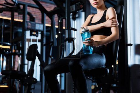 Photo for Cropped view of woman in sportswear sitting and holding sport bottle in gym - Royalty Free Image