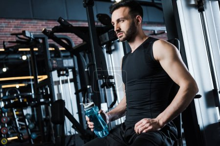 Photo for Low angle view of handsome sportsman in sportswear holding sport bottle in gym - Royalty Free Image