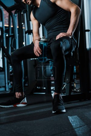 cropped view of man sitting and holding sport bottle in gym