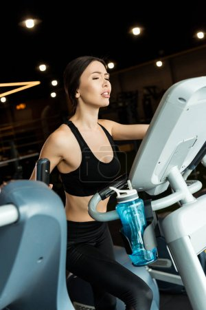 Photo pour Selective focus of displeased young woman in sportswear working out on exercise bike - image libre de droit