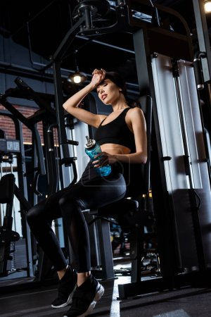 Photo for Low angle view of tired woman sitting and holding sport bottle in gym - Royalty Free Image