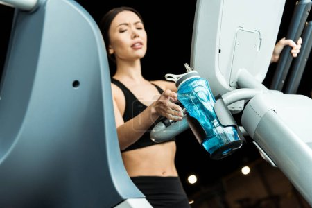 Photo pour Selective focus of athletic woman taking sport bottle while working out on exercise bike - image libre de droit
