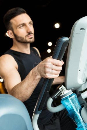 Photo for Selective focus of sport bottle near athletic man working out on exercise bike - Royalty Free Image