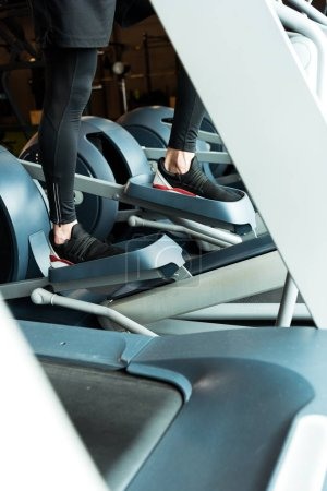 Photo pour Cropped view of sportsman working out on exercise bike in gym - image libre de droit