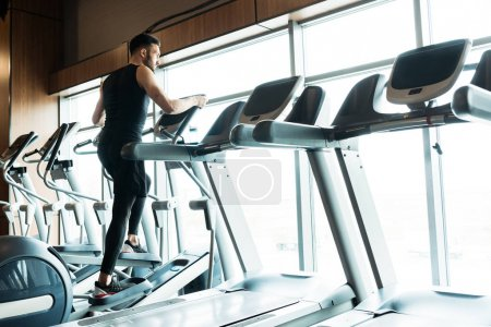 Photo for Low angle view of athletic and handsome man working on out on exercise bike in gym - Royalty Free Image