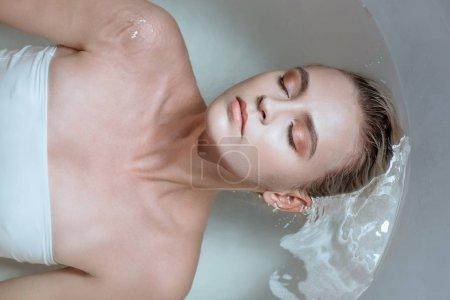 Photo pour Vue de dessus de femme sexy avec les yeux fermés dans la baignoire - image libre de droit