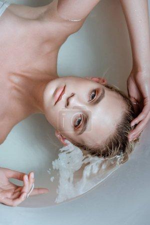 Photo pour Vue de dessus de la femme sexy regardant la caméra tout en étant couché dans l'eau claire dans la baignoire - image libre de droit