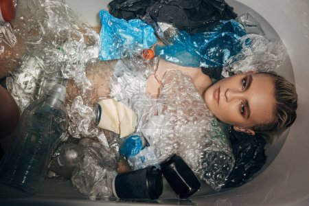Photo for Top view of beautiful woman among plastic rubbish in bathtub, eco concept - Royalty Free Image