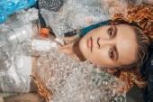 """Постер, картина, фотообои """"верхний вид молодой женщины в ванной с пластиковыми отходами, концепция загрязнения окружающей среды"""""""