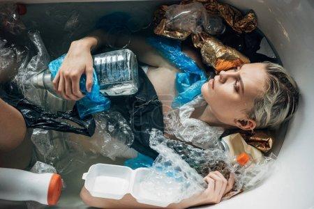 Photo pour Vue supérieure de la jeune femme triste se trouvant dans la baignoire avec la poubelle, concept de pollution environnementale - image libre de droit