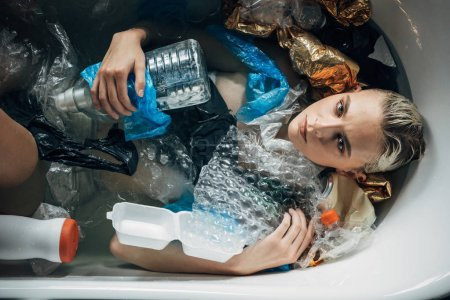 top view of young woman posing in bathtub with plastic trash, environmental pollution concept