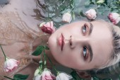 "Постер, картина, фотообои ""top view of beautiful woman lying in clear water among flowers and looking away"""