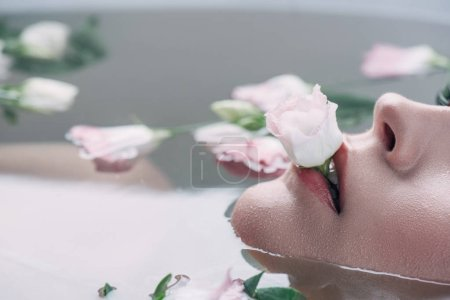Photo for Partial view of beautiful woman lying in clear water with rose in mouth - Royalty Free Image