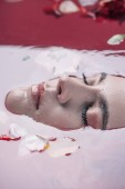 """Постер, картина, фотообои """"close up view of beautiful woman with closed eyes in pink water with rose petals """""""
