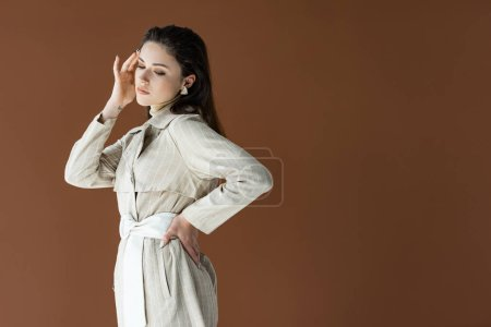 Photo for Fashionable woman in trench coat isolated on brown with hand on hip - Royalty Free Image