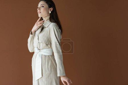 Photo pour Femme élégante dans le trench-coat à la mode d'isolement sur le brun, regardant loin - image libre de droit