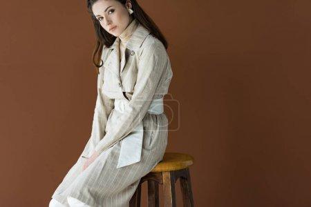 Photo pour Femme à la mode s'asseyant sur la présidence d'isolement sur le brun, regardant l'appareil-photo - image libre de droit