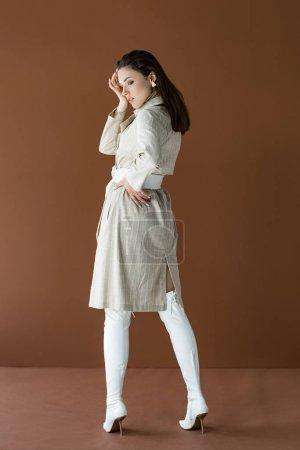 Photo pour Femme élégante dans le trench à la mode beige et les bottes blanches d'isolement sur le brun - image libre de droit