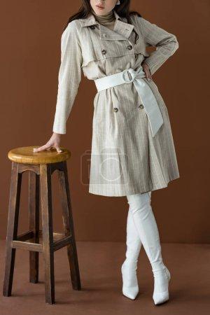 Foto de Vista recortada de la mujer de moda en elegante abrigo de trinchera de pie cerca de la silla aislada en marrón - Imagen libre de derechos