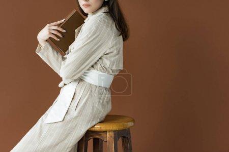 Photo pour Vue recadrée du jeune livre de tenue modèle, assis isolé sur brun - image libre de droit