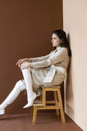 Photo for Side view of beautiful and trendy woman sitting on stairs, looking away - Royalty Free Image