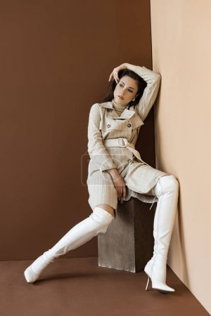 Foto de Fashionable woman in trench coat and white boots looking away on brown background - Imagen libre de derechos