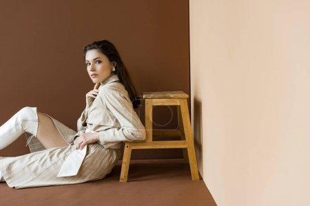 Photo pour Modèle à la mode en trench-coat et bottes blanches s'asseyant sur l'étage, regardant l'appareil-photo - image libre de droit