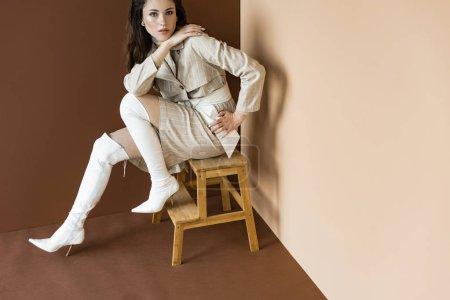 Foto de Vista de ángulo alto del modelo de moda en elegante abrigo de trinchera sentado en escaleras de madera - Imagen libre de derechos