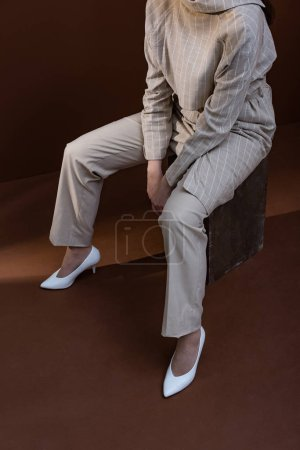 high angle view of fashionable woman in stylish wear sitting on brown background