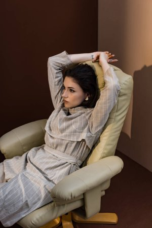 Photo for High angle view of attractive woman sitting on chair, looking away - Royalty Free Image