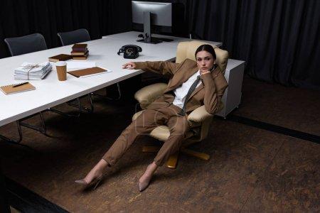 Photo pour Vue grand angle de succès et belle femme d'affaires assise sur un fauteuil dans le bureau, regardant loin - image libre de droit