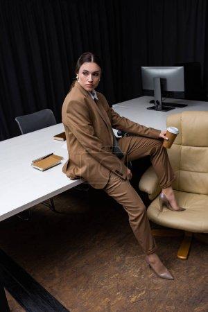Foto de Exitosa y hermosa mujer de negocios sentada en la mesa con la taza de papel en la mano, mirando hacia otro lado - Imagen libre de derechos