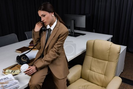 Photo for Fashionable businesswoman in suit talking on phone, sitting on table, looking away - Royalty Free Image
