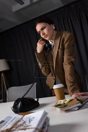 Photo pour Vue à angle bas de triste femme d'affaires avec combiné à la main parlant au téléphone, regardant loin - image libre de droit