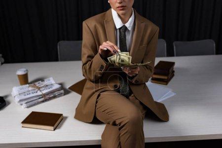 Foto de Vista recortada de la empresaria exitosa sentada en la mesa, cruzando las piernas y contando dinero - Imagen libre de derechos